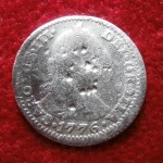 This Spanish silver coin, a one real, shows some obvious wear and tear, but it has a clear, sharp date of 1776. The date was most appropriate is it was found only a few days before the 4th of July.